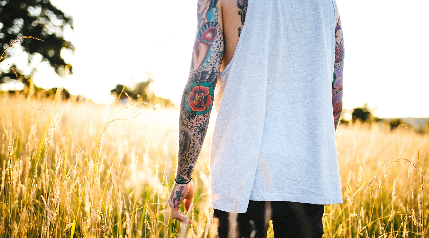 A person with full sleeve tattoos walks through a sun-drenched field.